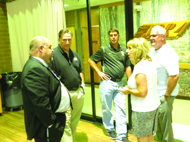 Hancock County Schools Superintendent Timothy Woodward (far left) spoke with Hancock County Commissioner Jeff Davis (far right) and his wife, Cindy Davis, during a meet-and-greet session Monday at the John D. Rockefeller IV Career Center, serving as a formal welcome to Woodward, who started his duties at the beginning of the month. Also pictured with Woodward and the Davises are (from left of center) district director of secondary curriculum and career and adult education Dan Enich and Oak Glen High School principal Dave Smith. (Photo by Steve Rappach)