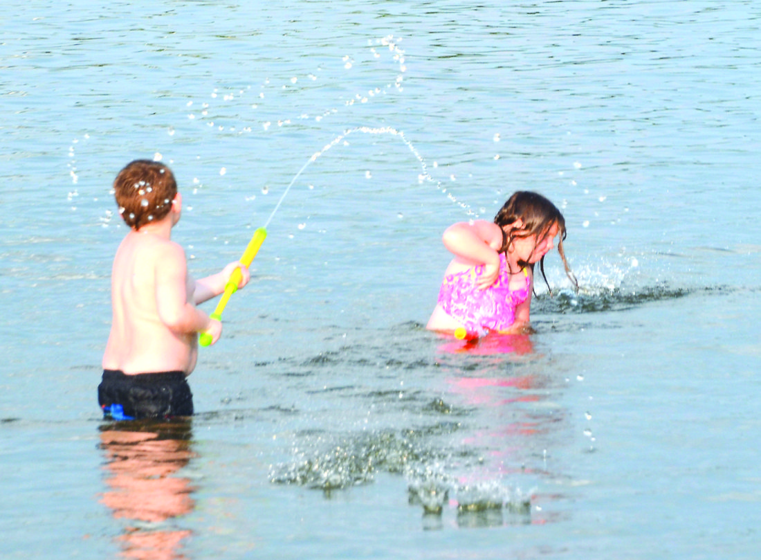 Twin five-year-olds Patrick and Irelynn Hill of East Liverpool enjoyed getting some target practice at each other with their squirt guns while swimming in Guilford Lake recently. (Photo by Patti Schaeffer)
