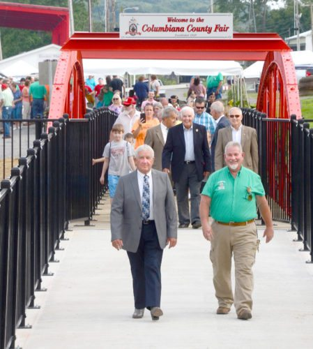 Following the dedication ceremonies, honorees and attendees were invited to follow County Engineer Bert Dawson and Columbiana County Fair Board President John Wolf across the historic bowstring arch bridge walkway. (Photo by Patti Schaeffer)