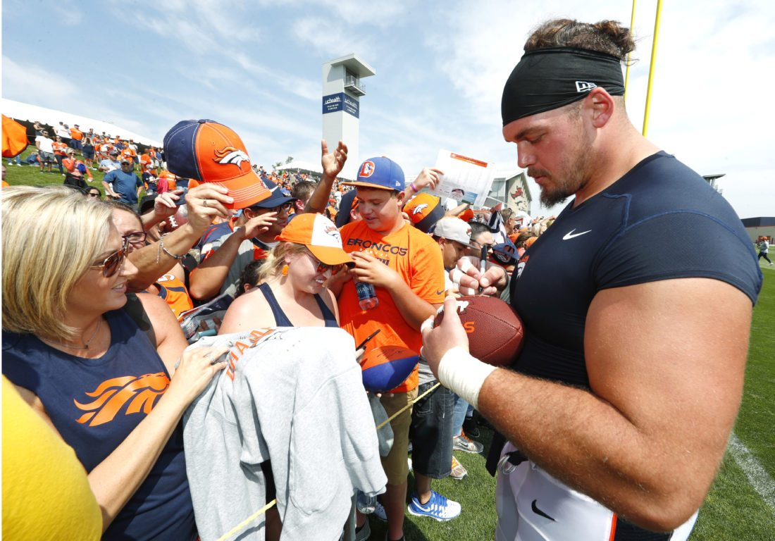 Denver Broncos defensive end Derek Wolfe signs autographs for fans after practice at an NFL football training camp, Saturday, Aug. 5, 2017, in Englewood, Colo. (AP Photo/David Zalubowski)