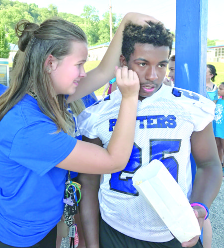 East Liverpool Potters football player Lane Kopras had his face painted by cheerleader Madelyn DeLong during the district's Back to School Bash. The event included giveaways, food, a petting zoo and bounce houses as well as free haircuts and bus registration. (Photo by Jo Ann Bobby-Gilbert)
