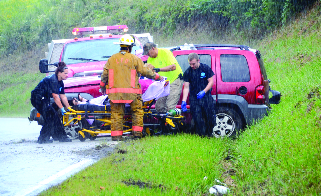 Jody Kireta of East Liverpool was transported by North Star Critical Care to East Liverpool City Hospital with injuries that were not life threatening after she rolled her 2005 Jeep Liberty on Middle Branch Road in Elkton around 2:30 p.m. Thursday. According to the investigating trooper, Megan Faith, Kireta was westbound on Middle Beaver Road and said the road became wet and slippery, and she lost control of the Jeep. It left the right-hand side of the road on a curve, striking the embankment and rolling over before coming to a stop upright. Trooper Faith said Kireta will be cited for failure to control. Lisbon Fire Department provided traffic control at the scene. The vehicle was removed by Calcutta Towing.  Pictured, Lisbon Assistant Fire Chief Gilbert Flory and Lt. Doug Rohm help North Star personnel to remove Jody Kireta and transport her to East Liverpool City Hospital. (Photo by Patti Schaeffer)