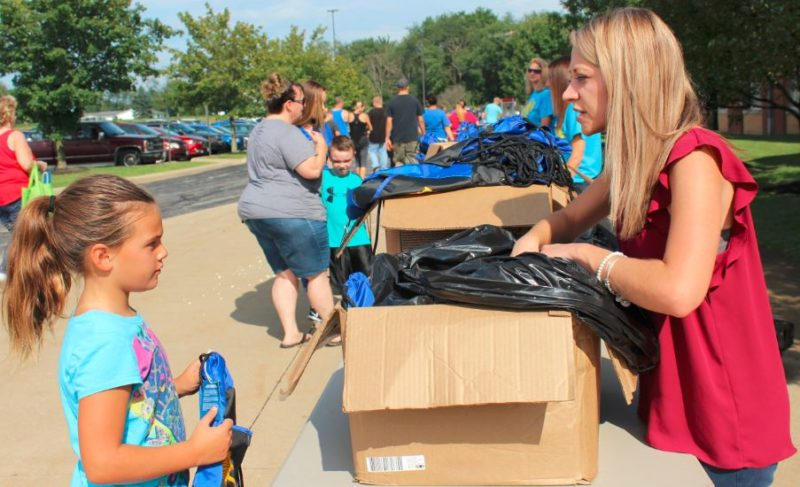 "Angela Sheldon (right), a district occupational therapist, readies a book bag for first-grader Katie Kellogg of Salineville during Southern Local Schools' seventh annual ""Back to School Bash"" held last week at the K-12 campus. (Submitted photo)"