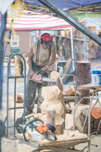Woodcarver Rick Cox works on his latest creation Tuesday during the 71st annual Hookstown Fair, which runs through Saturday, Aug. 26. Cox has been producing woodcarvings for 14 years, while his wife has 11 years of experience. Some of  their work includes bears, benches, and statues. The Fair is open 9 a.m. weekdays and 8 a.m. Saturday. Rides open 2 p.m. weekdays, 11 a.m. Saturday. The fairgounds are located along state Route 168 in Hookstown. (Photo courtesy of Jimmy Joe Savage)