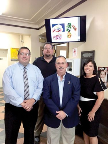 Those visiting East Liverpool City Hall will be able to obtain information on a variety of topics with this new televised system paid for with a grant secure by the health department. Shown with the system are (from left) Mayor Ryan Stovall; Service-Safety Director Brian Allen; Steve Hall, ER, East Liverpool Elks Lodge 258; and health Commissioner Carol Cowan. (Submitted photo)