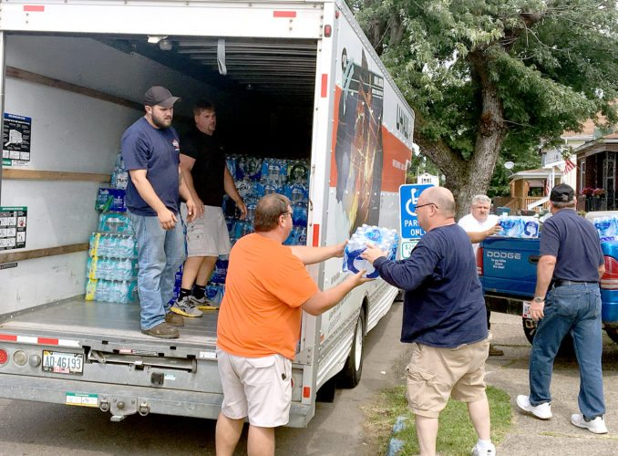 Volunteers and members of the Joshua Project and Living Well Church, 17th Street, Wellsville, on Wednesday loaded up a U-Haul truck with bottled water, donated to Hurricane Harvey victims in Texas. The Joshua Project organized the mission, collecting donations throughout the county. The water will be taken to Steubenville, where it then will be loaded on a tractor-trailer that is headed toward the Houston area to help with relief efforts. Volunteers also received donations at Save-A-Lot and Wellsville First Christian Church. (Photo by Steve Rappach)