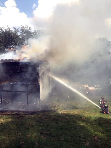 Flames shoot through the roof as East Liverpool firefighters pour water onto a vacant Haywood Street house they found fully involved upon arrival just before noon Monday. (Submitted photo)