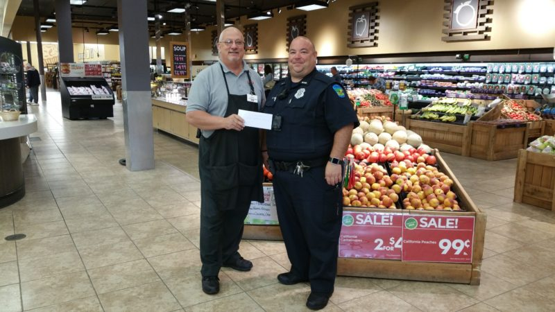 "Buddy Robinson (left), manager of the Calcutta Giant Eagle, presents a $500 check to St. Clair Township Police FOP 210 President Chris Davis from food sales proceeds that Giant Eagle during the ""Red, White and Thin Blue Line Community"" event that took place earlier this month. (Submitted photo)"