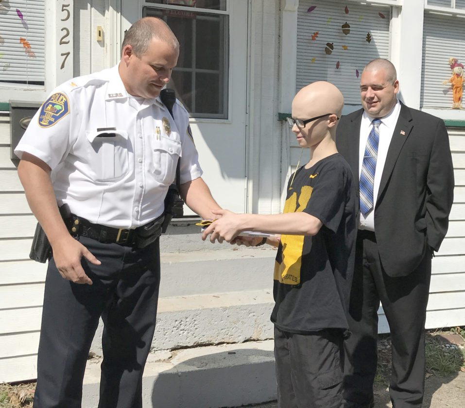 A stack of police department patches and letters was presented Thursday by East Liverpool police Chief John Lane to Wellsville teenager Gavin Campbell, who hopes to become a police officer one day. Also shown is Mayor Ryan Stovall. (Photo by Jo Ann Bobby-Gilbert)