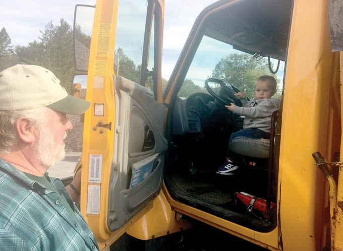 Two-year-old Jacob Mitchell took the wheel of Madison Township truck no. 2 as his grandfather, township road foreman Gary Mitchell, watched on during an open house Saturday at the new Madison Township Garage on state Route 45. The event, hosted by township trustees, gave residents an opportunity to view the updated fleet of equipment and tour the new facility. (Photo by Steve Rappach)