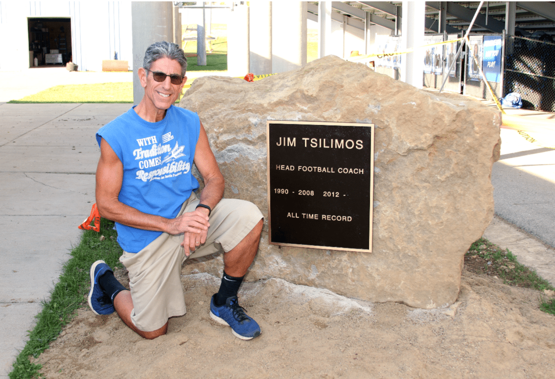 Lisbon High School football coach Jim Tsilimos kneels next to the memorial stone bearing his name placed outside War Memorial Stadium. Earlier in the season, Tsilimos set the school record for most career winds, eclipsing Bud Bucher. The stone was revealed during a surprise ceremony held by school officials prior to last week's school board meeting. (Submitted photo)