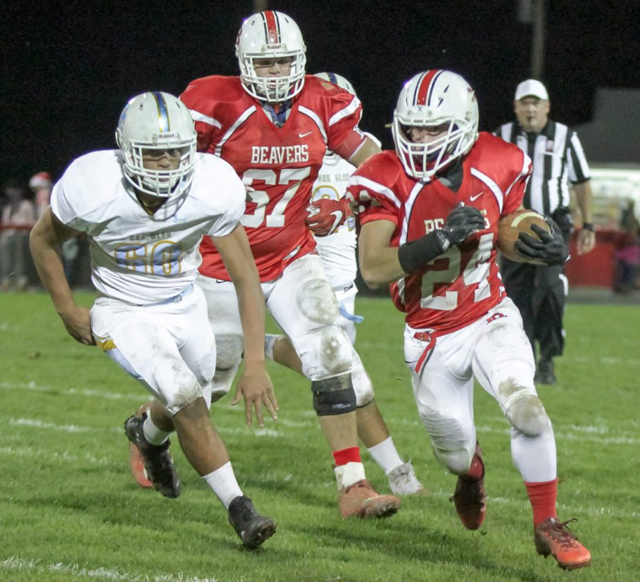Beaver Local's Torey Calio runs as Oak Glen's Cam Oulds pursues on Friday at Beaver Local High School. Also shown is Beaver Local's Zach Thomas.