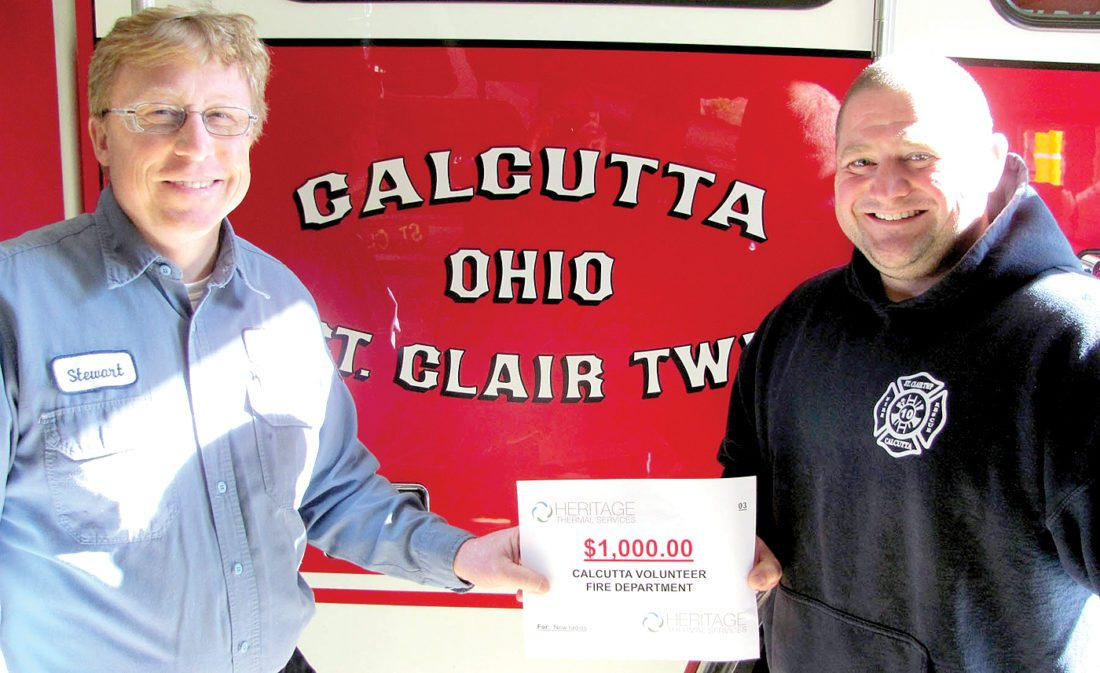 """Calcutta Volunteer Fire Department Capt. Jon Yerkey (right) accepts a $1,000 donation from Heritage Thermal Services Vice President Stewart Fletcher. The department will use the donation to purchase a pair of portable radios. Heritage reached out to local volunteer departments during National Fire Prevention Week in October to """"thank them for their service and to offer support for any equipment they might need,"""" a release states. In addition to Calcutta, the company has donated $1,000 each to the Glenmoor and Liverpool Township VFDs to help fund the purchase of new equipment. (Submitted photo)"""