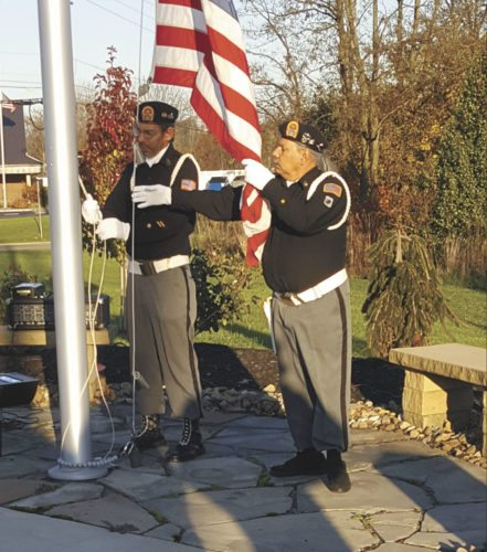 Members of the Salem Amvets Post 45 raise the flag on the pole at the corner of Saltwell Road and North Market Street Thursday during Family Recovery Center's Tribute to Veterans. (Submitted photo)