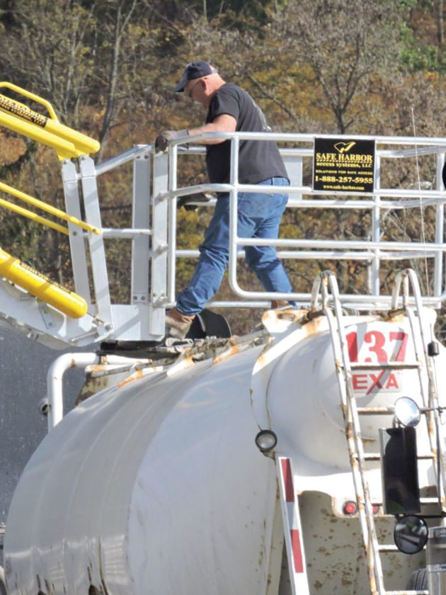 """An employee works on a """"sand can"""" truck, which is used to transport sand to Marcellus and Utica shale natural gas fracking sites, at the Transload Solutions site in Benwood. (Photo by Casey Junkins)"""