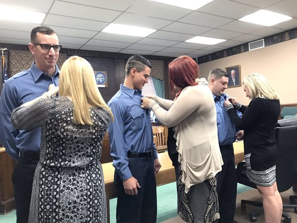New East Liverpool city firefighters had their badges pinned after being sworn in Friday morning by Municipal Court Judge Melissa Byers Emmerling. Shown are (from left) Andrew Wolfgang and wife Lauren, Michael Dubray Jr. and wife Courtney, and Derek Sullivan and girlfriend Melanie Weimer. (Photo by Jo Ann Bobby-Gilbert)