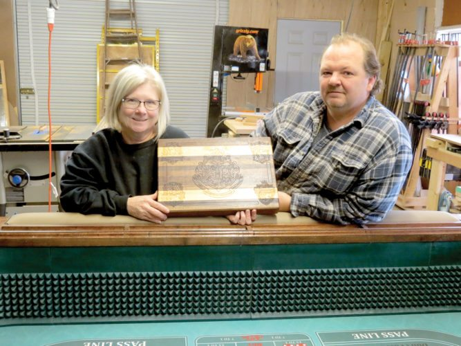 Ellouise and Brad Shirley, owners of the Riverside Woodshop — a local artisan shop located at 812 Main St., Wellsville, specialize in custom-made furniture and decor. Here, the Shirleys stand behind recently finished custom craps table, while Mrs. Shirley holds a custom-engraved carving board with the four houses and coat of arms of Hogwarts School of Witchcraft and Wizardry from the Harry Potter series of books. Both items were made inside the shop. (Photo by Steve Rappach)