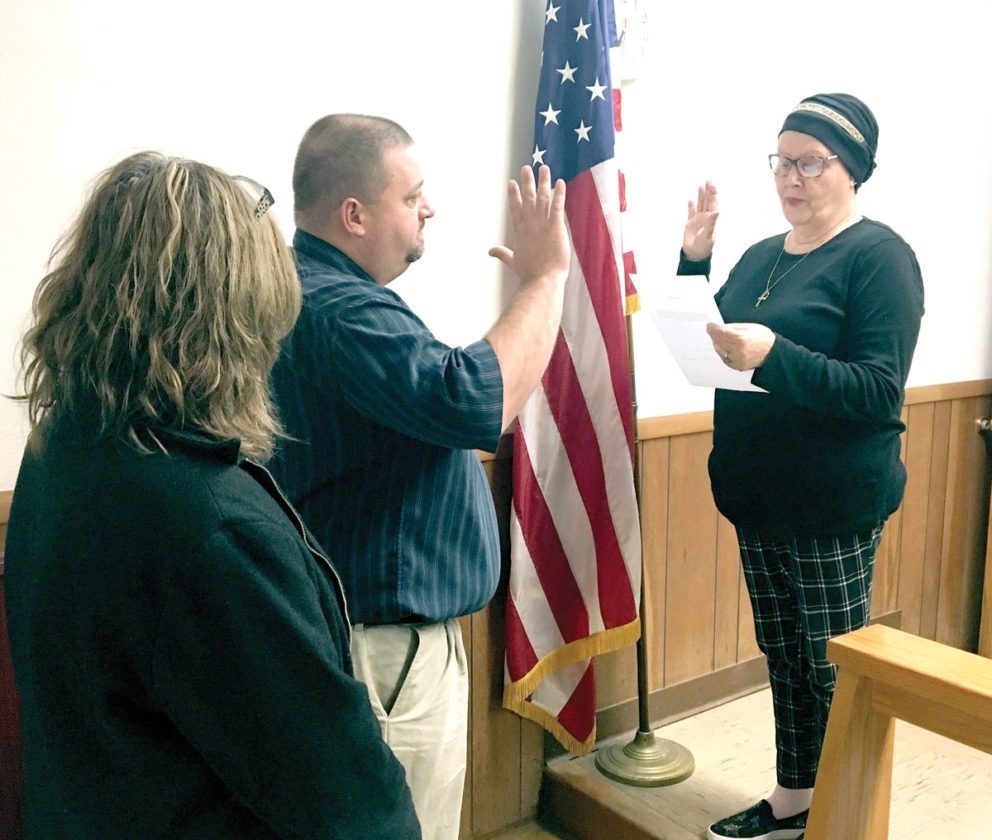 Frank Thorne (center) is sworn-in by Wellsville Mayor Nancy Murray (right) as the village's newest full-time firefighter during Tuesday's Village Council meeting. Standing behind Thorne is his girlfriend, Jean Pastore. (Photo by Steve Rappach)