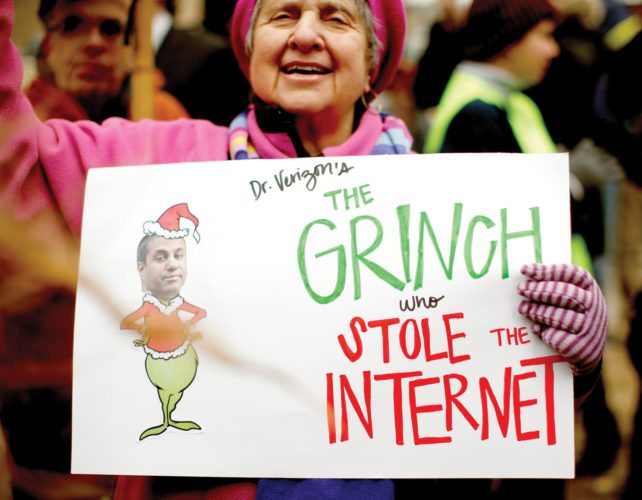 "Diane Tepfer holds a sign with an image of Federal Communications Commission (FCC) Chairman Ajit Pai as the ""Grinch who Stole the Internet"" as she protests Thursday near the FCC, in Washington. (AP Photo/Carolyn Kaster)"