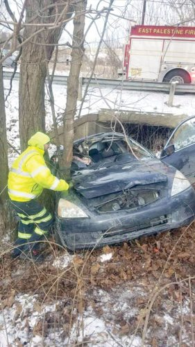A New Waterford firefighter checks a damaged vehicle after a single-car crash on Waterford Road Thursday. (Photo courtesy of East Palestine Fire Department)