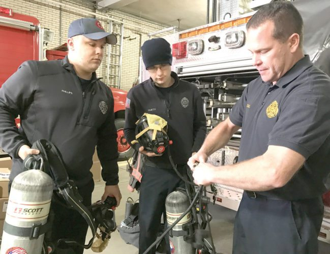 With assistance from (from left) firefighters Dave Phillips and Lance Smith, East Liverpool Assistant Chief David Edgell shows how connectors on the new air packs purchased by the city department can be used by firefighters to share air from one tank. (Photo by Jo Ann Bobby-Gilbert)