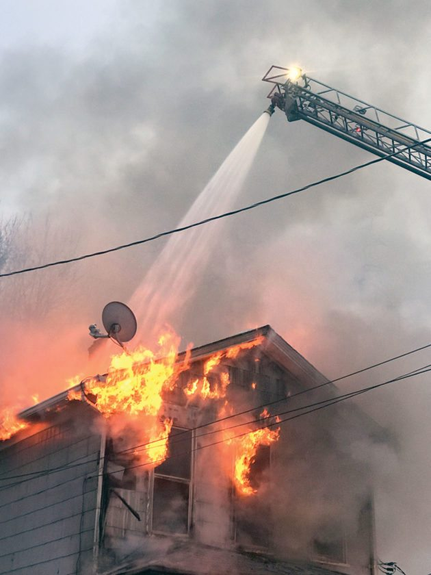 The aerial truck pours a deluge of water onto the roof of a Ravine Street house in East Liverpool where flames ripped through the roof Wednesday morning, injuring the owner and killing his dog. (Photo by Jo Ann Bobby-Gilbert)