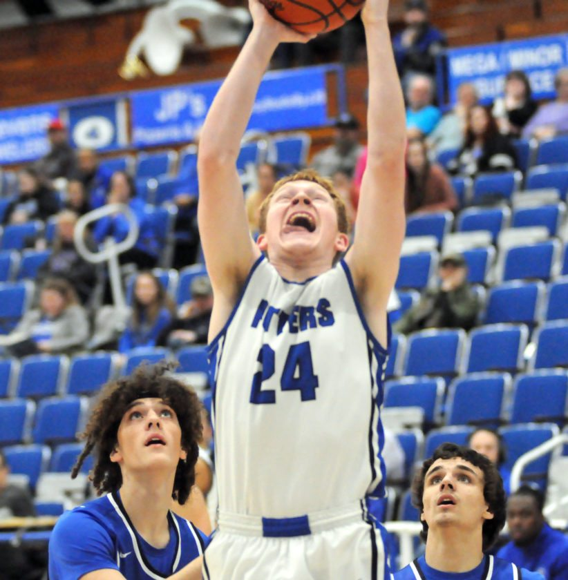 At left, East Liverpool's Izaiha Browning goes for a layup as Harrison Central's Evan Stine (left) and Chance Hursey look on during Tuesday's game at Potter Fieldhouse.