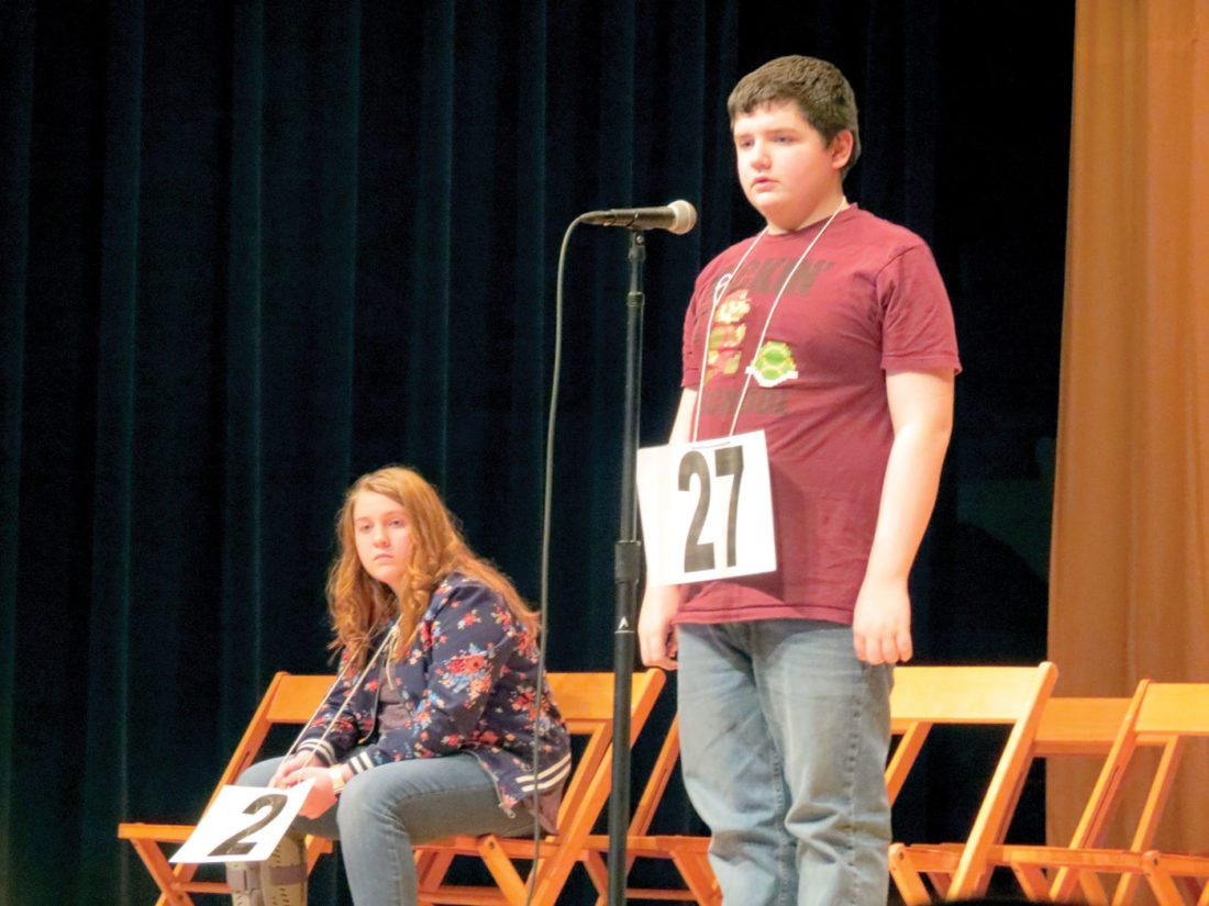 "Wellsville seventh grader Connor Hooper stood at the microphone at Thursday's Wellsville Spelling Bee, held at the Wellsville High School auditeria, while sixth grader Aliya Boso watched on. Hooper claimed his second consecutive school bee championship Thursday by correctly spelling ""toucan"", while Boso was the school bee's runner-up. Both spellers, along with third place speller Colton Carter, will compete at the Columbiana County Spelling Bee on March 7 at the David Anderson High School Auditorium in Lisbon. (Photo by Steve Rappach)"