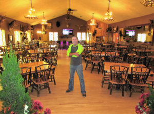 The Cross Eyed Moose event center is open for its fourth year and offers a unique atmosphere for special events like weddings, reception, rehearsals, holiday parties, trade shows and anniversaries and like events. Located at 23250 Main St. in Homeworth, it is in a lodge setting with a stone-faced bar, reception center and a 72-inch flat screen television in the upper level. Greg Hoover, who owns the facility with his wife, Connie, is pictured in the upper level where the seating capacity will accommodate 120 guests under a vaulted ceiling. (Salem News photo by Larry Shields)