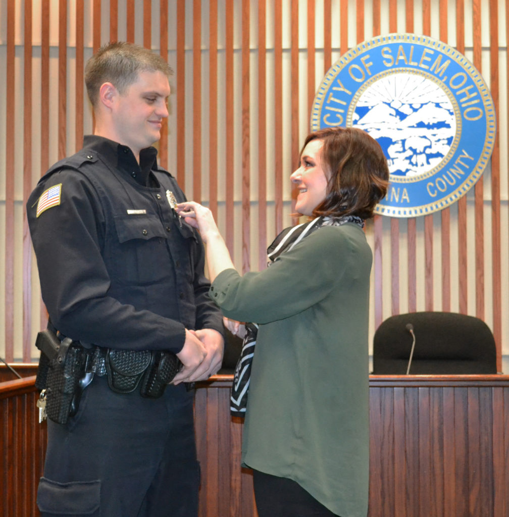 Salem Police Patrolman Matthew Cochran stands at attention as his wife Angela pins on his badge during his swearing-in as a full-time officer Thursday morning. Mayor John Berlin administered the oath. An East Liverpool native, Cochran joined the department three years ago as a part-timer and will take the place of Patrolman Steve LaRosa on the road. LaRosa has been named handler for Salem's second K-9 unit and will begin training next month with his canine partner. (Photo courtesy Salem Police)
