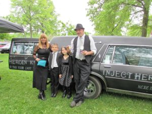 """During the Steps of Change, OhioCAN drug addiction awareness program in Centennial Park Saturday, the recently commissioned Heroin Hearse Awareness vehicle appeared with its message that heroin kills. Based in Huntington, W.Va., owner Dwayne Woods and his partner Trish Burns, along with Woods' two children, Brandon, 10 and Victoria, 8, talked with many of the 500 or so people who attended the event. Woods said it's all about awareness and wiping out the stigma associated with addiction. He said its better to talk face-to-face with people. """"I want to start a fire in your heart and mind,"""" he said. Barnes holds a """"Project Dawn"""" kit that includes Narcan, a medication that can reverse an overdose caused by an opioid drug, heroin or prescription pain medications, while Woods displays Evzio, an auto-injected prescription medicine used in opioid emergencies such as an overdose. (Salem News photo by Larry Shields)"""