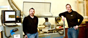 Rob Roberts (left) and Eric Thorne, both 1991 graduates of Salem High School, are shown with a lathe at their SabreCat Bat Company in Louisville, Ohio. Cincinnati Reds' Scooter Gennett used one of their bats to hit four home runs in a game June 6. The bat is now on display at the Baseball Hall of Fame. (Submitted photo)