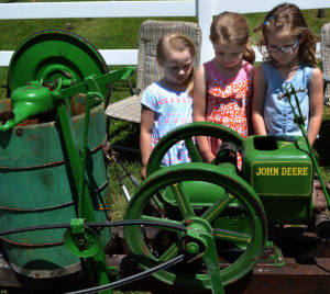 Among the youngsters attending  the Winona Strawberry Festival were Cope family members, from left, 4-year-old Clara, 6-year-old Ava and 5-year-old Hadley of Salem shown checking out an old-fashioned ice cream maker. (Salem News photo by J.D. Creer)
