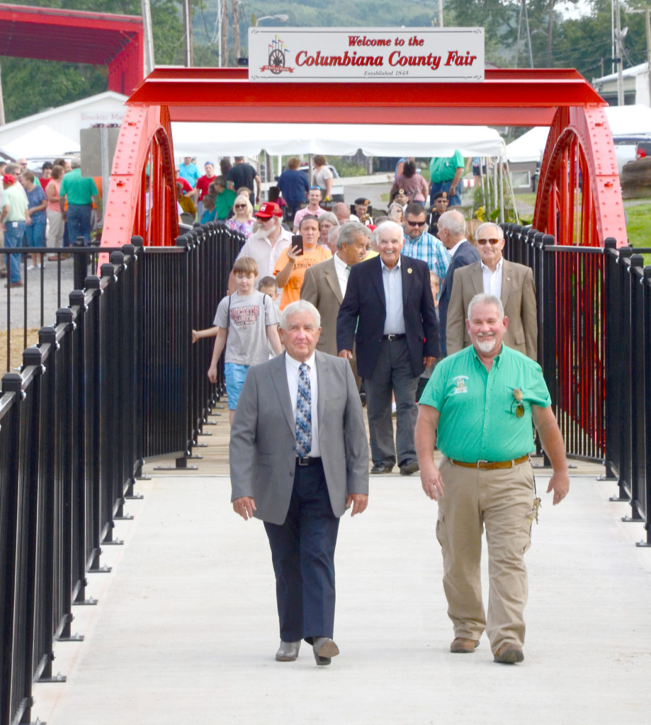 Following the dedication ceremonies, honorees and attendees were invited to follow County Engineer Bert Dawson and Columbiana County Fair Board President John Wolf across the historic bowstring arch bridge walkway as they led a tour to the newly re-constructed administration offices. (Salem News photos by Patti Schaeffer)