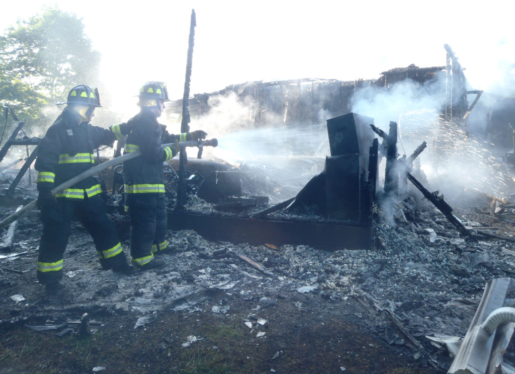 West Point firefighters Deanna Chamberlain and Zach Lawrence hose down the charred remains of the garage in Elkrun Township that was destroyed by fire Wednesday morning. The attached house was also heavily damaged. (Salem News photo by Tom Giambroni)