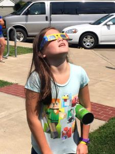 Hannah McPeek of Columbiana views the sun with solar eclipse glasses Monday at the Lepper Library in Lisbon while holding her homemade pinhole camera made from a Pringles can. (Salem News photo by Katie White)