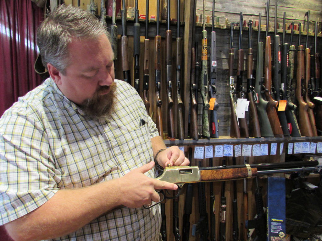 Jason Burtz, owner of Burtzland Outfitters in Alliance, offers the most inexpensive firearm transfers around $15. Burtz said he can take care of customers who need   guns shipped in or out and can take care of all the paperwork. He is pictured making an adjustment to the rear sight of a Henry 45 lever action rifle, which is not an exact copy of the old Henry rifle, Burtz said. (Salem News photo by Larry Shields)
