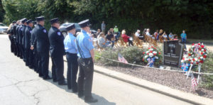 Wellsville police officers and firefighters stand at attention during Sunday's Sept. 11 ceremony. To their right is the Catherine Salter Memorial, in memory of the 1982 Wellsville High School graduate who was killed that day. (Salem News photo by Tom Giambroni)