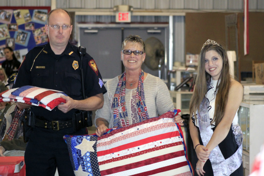 During an annual 9/11 service of recognition at the Columbiana County Fairgrounds on Sunday, Sgt. Donny Johnson of the East Palestine Police Department, above, received a quilt and a quilted dog bed for K-9 Toney. Presenting him the handmade items are Ginger Riffee, the quilter, and Michalia Ayers. (Salem News photo by Deanne Johnson)