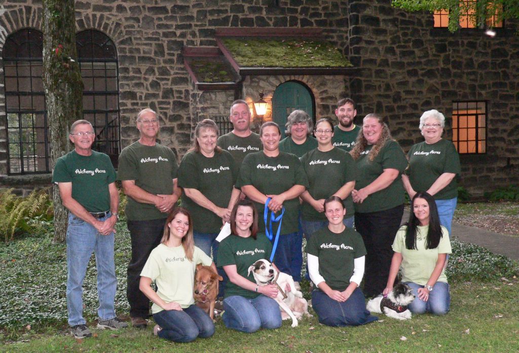 The Alchemy Acres Animal Sanctuary family poses for a portrait in front of their new home, a stone castle built in 1933 north of Rogers which they'll preserve as their new Event and Education Center, with plans to hopefully open in spring 2018. The secluded setting off of Adams Road includes 10 acres and an opportunity for 177 more acres for the relocation and expansion of the current Salem-based no-kill animal shelter and adoption facility. Pictured are: kneeling from left, Heather Drane, Chanel, Tricia Rogers, Buckeye, Brandi Burns, Sadie, and Cherri Piszczek; standing from left, Ken Richey, Steve Sacco, Julie Sacco, Steve Boyd, Emily Sacco, Kathy Monteleone, Katie Sacco, Andrew Grueber, Marie Hernandez and Debbie Steeb. (Salem News photo by Mary Ann Greier)