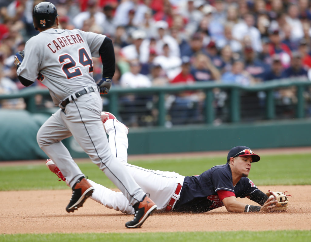 Cleveland Indians' Giovanny Urshela makes a diving stop and throws out Detroit Tigers' Jeimer Candelario at second base as Miguel Cabrera runs by during the eighth inning in a baseball game, Wednesday, Sept. 13, 2017, in Cleveland. The Indians defeated the Tigers 5-3 and set the American League record with 21 consecutive wins. (AP Photo/Ron Schwane)
