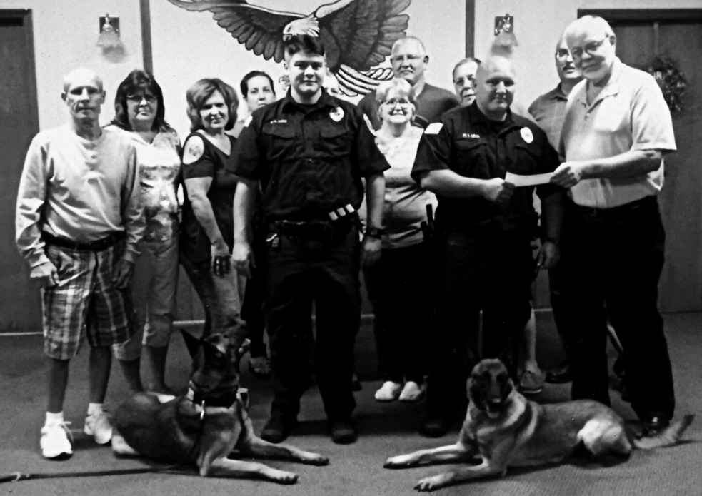 Salem Fraternal Order of Eagles 316 officers present a check for $2000 to Salem Patrolmen Steve Larosa and Mike Garber and their K-9 counterparts, Argo and Simon, for the police department's K-9 program. The Eagles hosted a breakfast, golf outing and steak dinner on Aug. 19 as a fundraiser for the K-9s. Pictured in front receiving the check from Trustee Ron Sanor are Simon, Garber, Larosa and Argo. Standing in the back, from left, are President Mike Glista, Vice President Tammy Wilson, Trustee Lisa Blythe, Secretary Monica Chestnut, Inside Guard Norm Miller, Conductor Donna Baker, Trustee Tim Chestnut, Treasurer Randy Baker and Lt. Dave Casto. (Submitted photo)