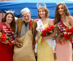 Johnny Appleseed, aka Sonny Reynolds, takes a break from passing out apples to pose with the 2017-2018 Johnny Appleseed Festival royalty: Becky Bernet, second attendant, Queen Samantha Moschgat and Abigail Monte, first attendant.