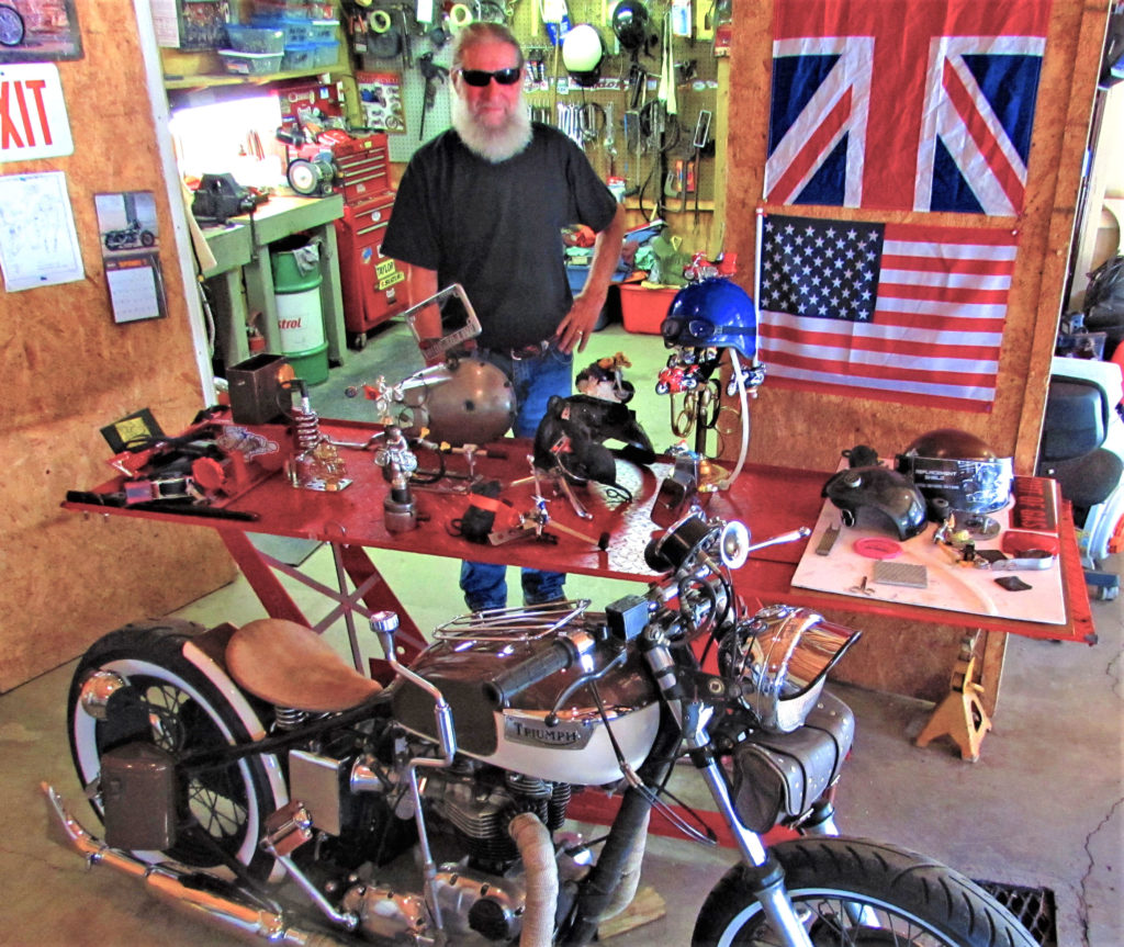 """The Power House Cafe (The old Side Door) will hold a bike show from 6 to 10 p.m. Sept. 29 to award trophies in four classes of motorcycles including first, second and third places in best stock, custom, chopper/bobber and rat bikes. Organizer Dwain Kale is pictured with his own award-winning Triumph """"Whitewall bike,"""" and 11 of the 12 custom hand-crafted trophies he made that will be awarded at the Power House bike show.  (Salem News photo by Larry Shields)"""