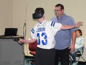Lisbon freshman Gabe Damron tries to keep his balance while experiencing a virtual reality simulation of walking on a beam atop the Sears Tower in Chicago in the Virtual Reality Lab at the Kent State University Salem campus. Also pictured is Clayton Gellatly, the IT manager at Kent State. The instructor in the classroom was Karen Guerrieri-Marr. Freshman and sophomores from Leetonia and Lisbon high schools visited the college Friday morning, interacting with campus instructors while taking part in activities dealing with math, science and technology. The STEM days continue the next two Fridays. The campus also plays host to guidance counselors from all districts for breakfast next Friday. (Salem News photos by Mary Ann Greier)