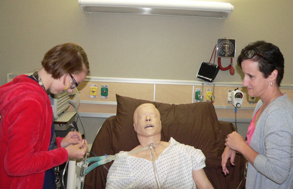 Leetonia freshman Layla Newton prepares to perform a procedure on a mannequin with direction from Kent State Salem nursing instructor Krista Hawkins during STEM days at the campus.