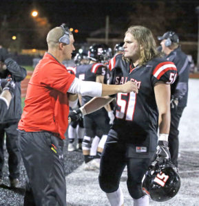Salem defensive coordinator Adam Doud talks to Robbie Sarginer during the Quakers game against West Branch last Friday. (Photo by Gary Leninger)