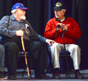 Lisbon veterans Arthur Matheny and WWII and Korean War Veteran Kenneth Bettis talk while on stage at the Lisbon High School Veterans Day program.