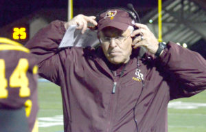 South Range coach Dan Yeagley adjusts his headset during the Raiders' game with Akron Manchester on Friday in Louisville. (Photo by Patti Schaeffer)