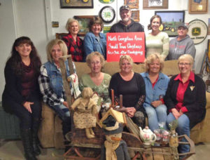 """Small Town Christmas 2017,"" the 10th annual tour of selected crafters and their shops in the North Georgetown area, will be held from 9 a.m. to 4 p.m. Nov. 24 and 25. Pictured are some of the shop owners, first row, from left, Lettie Davis, Bonnie Wise, Dianna Hawk, Susie Kaiser, Marilyn Foss, Cheryl Hrovatic; second row, Sue Caulfield, Loretta Mangun, Tye Caufield, Barb Caufield and Cindy Berger. Also shown is the sled loaded with gifts donated from the shops to be awarded to one lucky winner. (Submitted photo)"